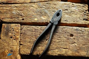 Плоскогубцы на деревянном столе