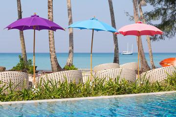 Swimming pool and beach chairs near the sea, Thailand