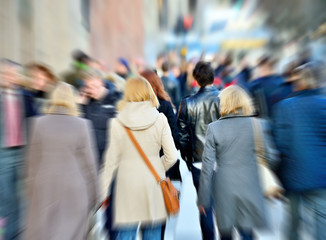 Zoom blurred pedestrians / shoppers on street