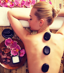 Woman relaxing in spa salon with hot stones on body.