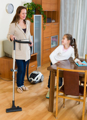 Woman and daughter cleans the house