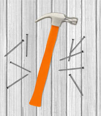 Hammer and nails over white wooden background