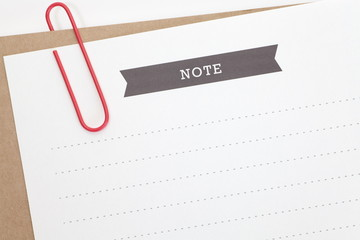 Blank paper note and red metal paperclip