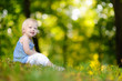Cute toddler girl sitting on the grass on summer