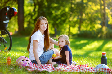 Young mother and her daughter picnicking