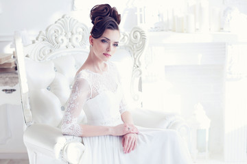 Young gorgeous bride is sitting in antique armchair