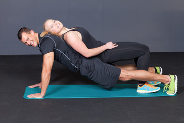 Body weight push up - woman laying on man doing push ups