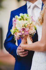 Close up of bride holding beautiful pink wedding flowers bouquet