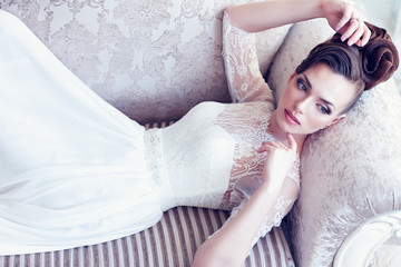 Young gorgeous bride is lying in antique couch