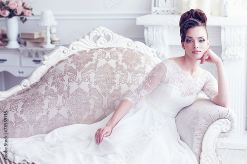 Fototapeta Young gorgeous bride is sitting in antique couch