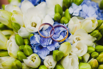 Golden wedding rings on bridal bouquet.