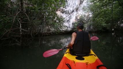 man rows kayak along river among mangrove brushwood to cliff
