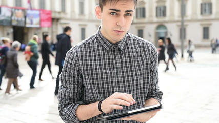 young handsome alternative dark model man in town using tablet
