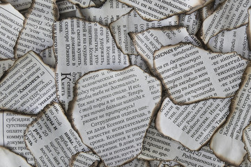 Burnt scraps of newspaper for background