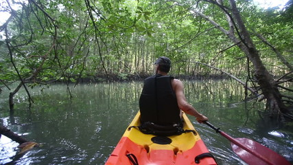 strong elder man rows kayak with paddles along river