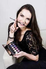 Beautiful girl with eyeshadow and brush