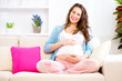Pregnant smiling woman sitting on a sofa and caressing her belly