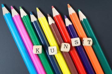 Buntstifte und Holzwürfel mit dem Wort Kunst