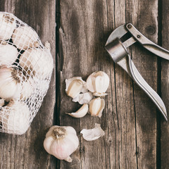 garlic and presser on vintage wood table background