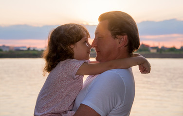 Dad with his little daughter on the riverbank