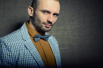 Portrait of handsome stylish man in trendy clothers, over canvas