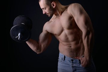 Strong athletic man with perfect body posing with dumbbells