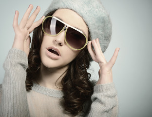 Fashion portrait of young pretty woman wearing sunglasses over b
