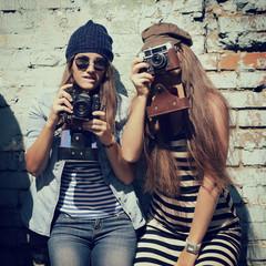 urban girls have fun with vintage photo cameras outdoor near gru