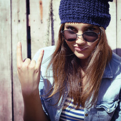 portrait of beautiful cool girl gesturing in hat and sunglasses,