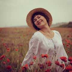 Cheerful attractive woman has fun on a poppy field, summer outdo