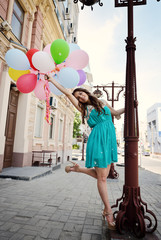 Happy romantic fashion girl with colorful balloons, outdoors. To