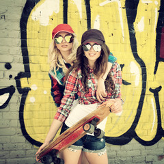 Two teen girl friends having fun together with skate board. Outd