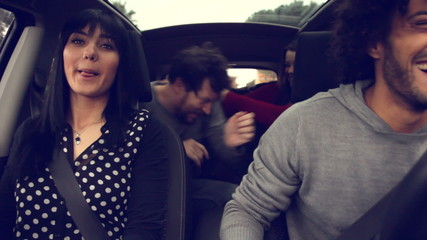 Four cool people dancing and laughing while driving car happy
