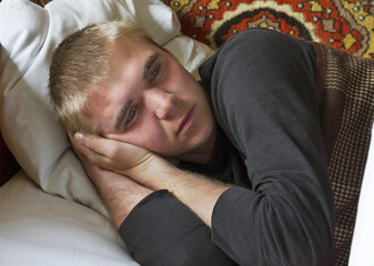 Young man in a bed.