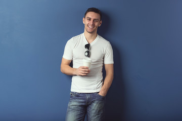 Young man in shorts and white t-shirt is smiling standing near