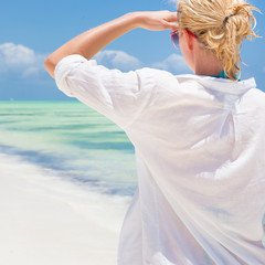 Woman on the beach in white shirt.
