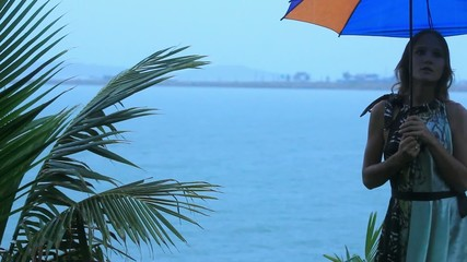 young woman on a tropical beach with umbrella in rainy season