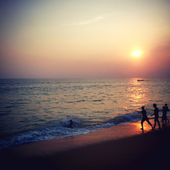 Sunset above the ocean with silhouette of children