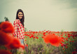 Young beautiful woman walking and dancing through a poppy field,