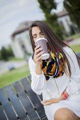 Beautiful teenage girl with phone and coffee