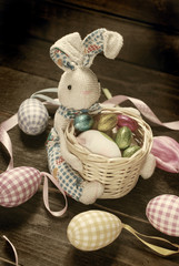 vintage easter decoration with bunny holding basket and eggs