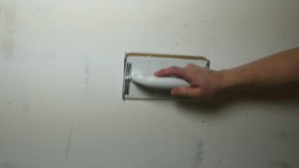 Man Hand Sanding Plaster Wall, close up