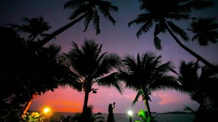 young woman photographs beautiful sunset near palms, lantern on