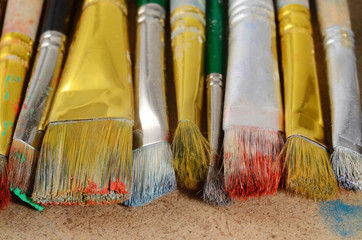Artist's desktop with old dirty colourful brushes on palette