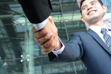 Handshake of businessmen with smiling face
