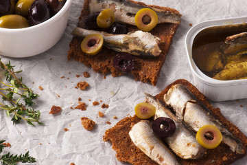 Sandwich, tapas with sardines, sprats with olives and herbs