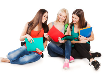 Three smiling college students sitting in a row against white