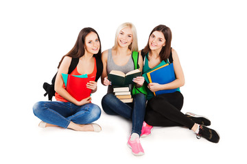 Three smiling college students with books sitting in a row
