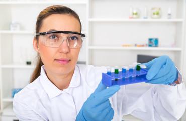 Chemist woman testing sample of liquid in laboratory