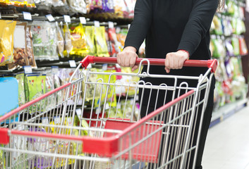 Lady pushing a shopping cart in the supermarket.